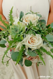 Succulents,ferns and mixed foliages accented with a few neutral blooms.
