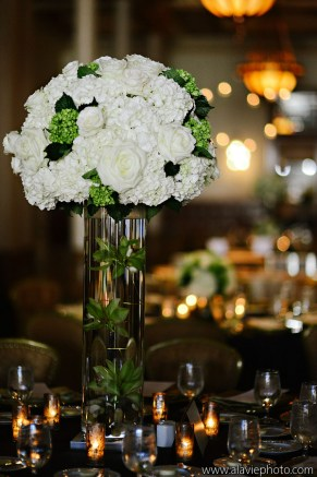 Formal tall centerpiece of white and green flowers.