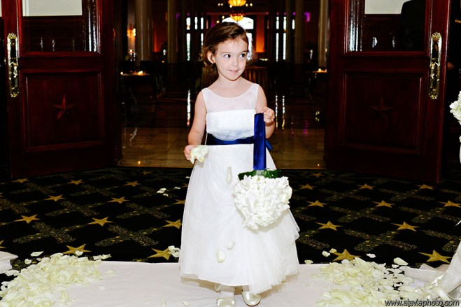 Adorable flower girl with purse covered in fresh flowers.