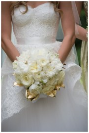 White spring bridal bouquet with white peonies and gold leaf accents.