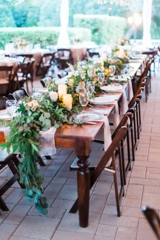 Vineyard tables featuring lush foliage garlands and candles.
