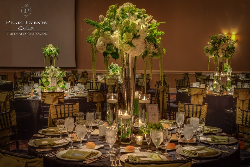 Tall centerpiece with candles, mercury glass, viburnum and ferns.