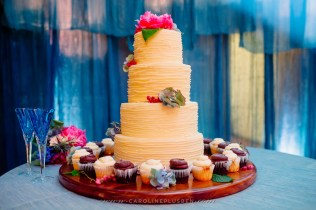 Rustic wedding cake with colorful blooms.