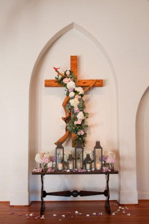 Floral embellished cross.Winter indoor ceremony.