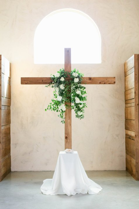 Rustic cross for indoor ceremony with foliage garland.