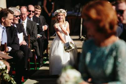 Flower girl with flower crown and box of petals to toss at outdoor ceremony.