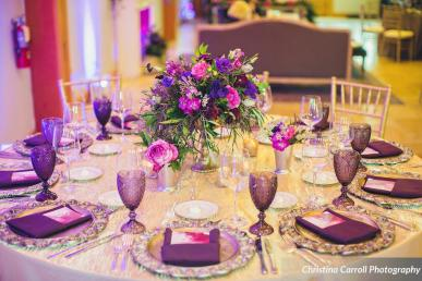 Low centerpiece with lush jewel toned flowers in mercury glass