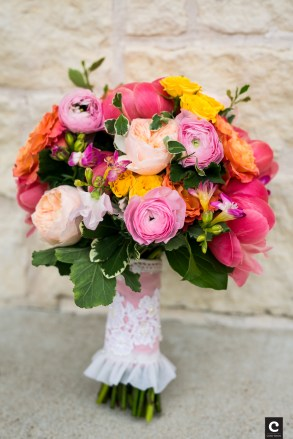 Coral peony, orange roses and pink ranunculi in a bridal bouquet.