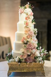 Blush and peach flowers cascading on wedding cake.