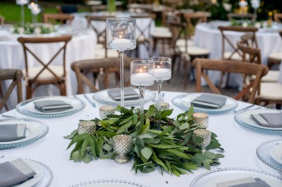 Candle and greenery centerpiece with mercury glass votives.