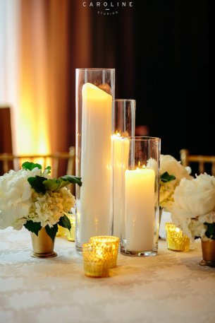 Centerpiece with flowers and candles in golds and whites.