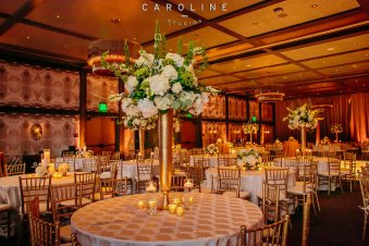 Tall wedding reception centerpiece in gold container.