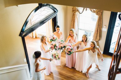 Bridesmaids with blush gowns and blush blooms.
