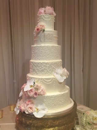 Wedding cake with 6 tiers with fresh flower accents.