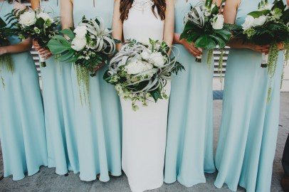 Bridesmaids in soft blue gowns and tropical bouquets
