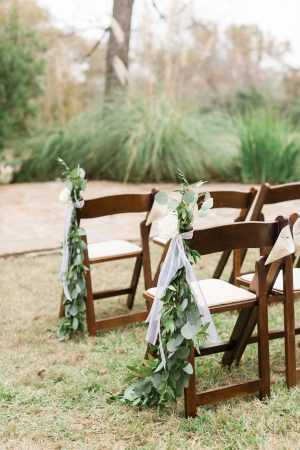 Silver dollar eucalyptus garland for chairs at outdoor ceremony.