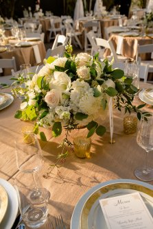 Low floral centerpiece of all white winter flowers; roses, mums, amaryllis, ranunucla, jasmine vine.