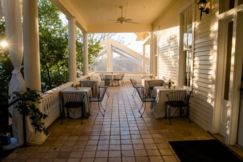 View of the porch at The Allan House set with bistro tables.