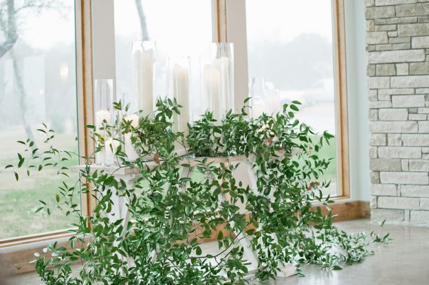 Smilax foliage accented oversized candles on altar table.