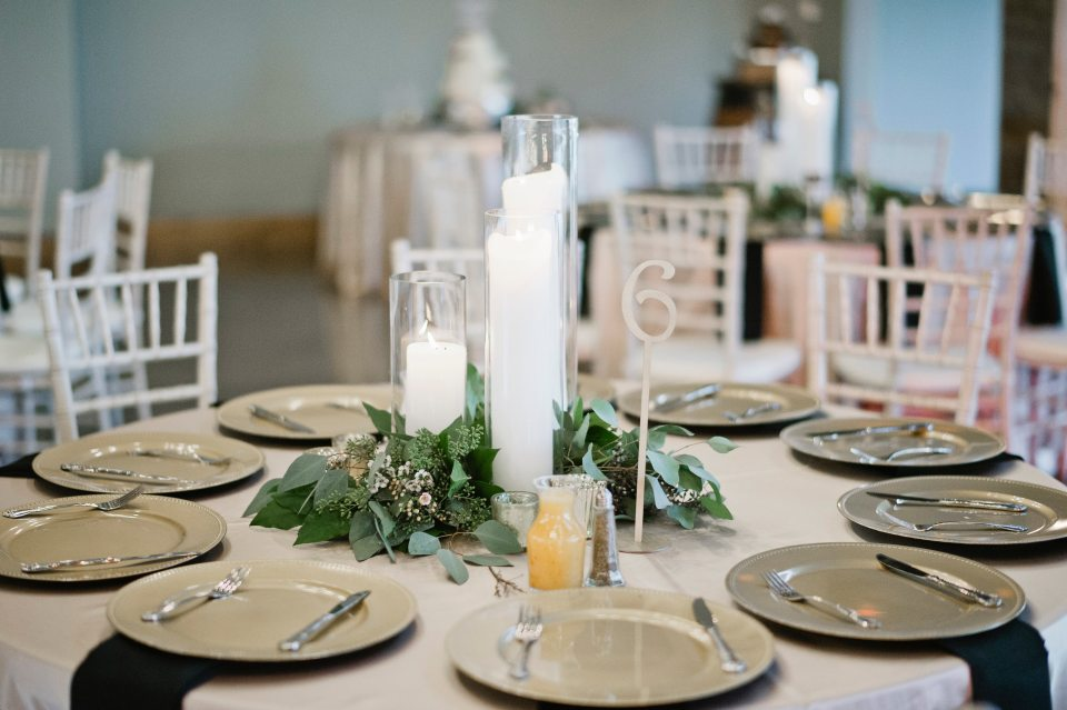 Trio of pillar candles accented with small clusters of greenery.
