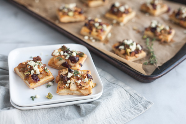 Caramelized Onion and Apple Tarts with Blue Cheese and Cranberries | BourbonandHoney.com -- These super flavorful Caramelized Onion and Apple Tarts with Blue Cheese and Cranberries are the perfect bite sized appetizer!