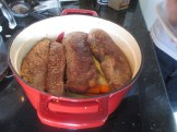 Short ribs being added to the cast iron pot