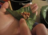 Grape leaf being stuffed on the palm of a hand