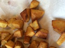 Fried potato cubes on a paper towel