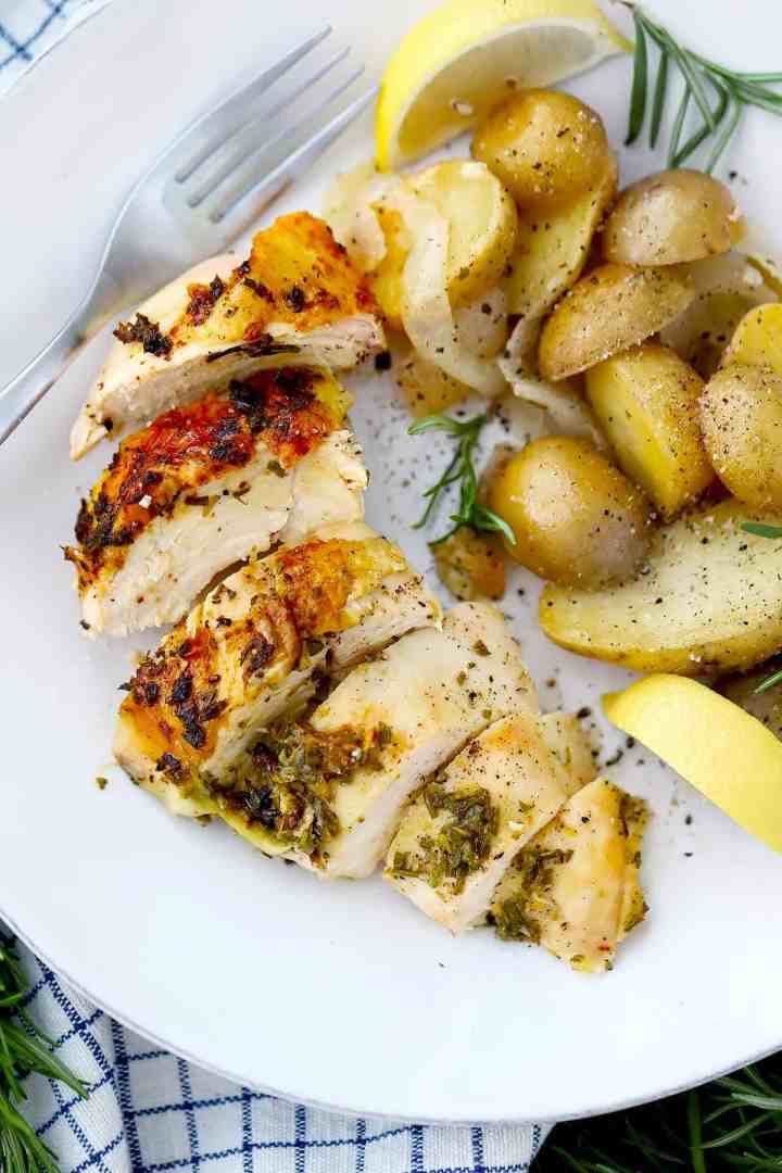 A sliced roasted chicken breast and potatoes on a white plate with a lemon slice.