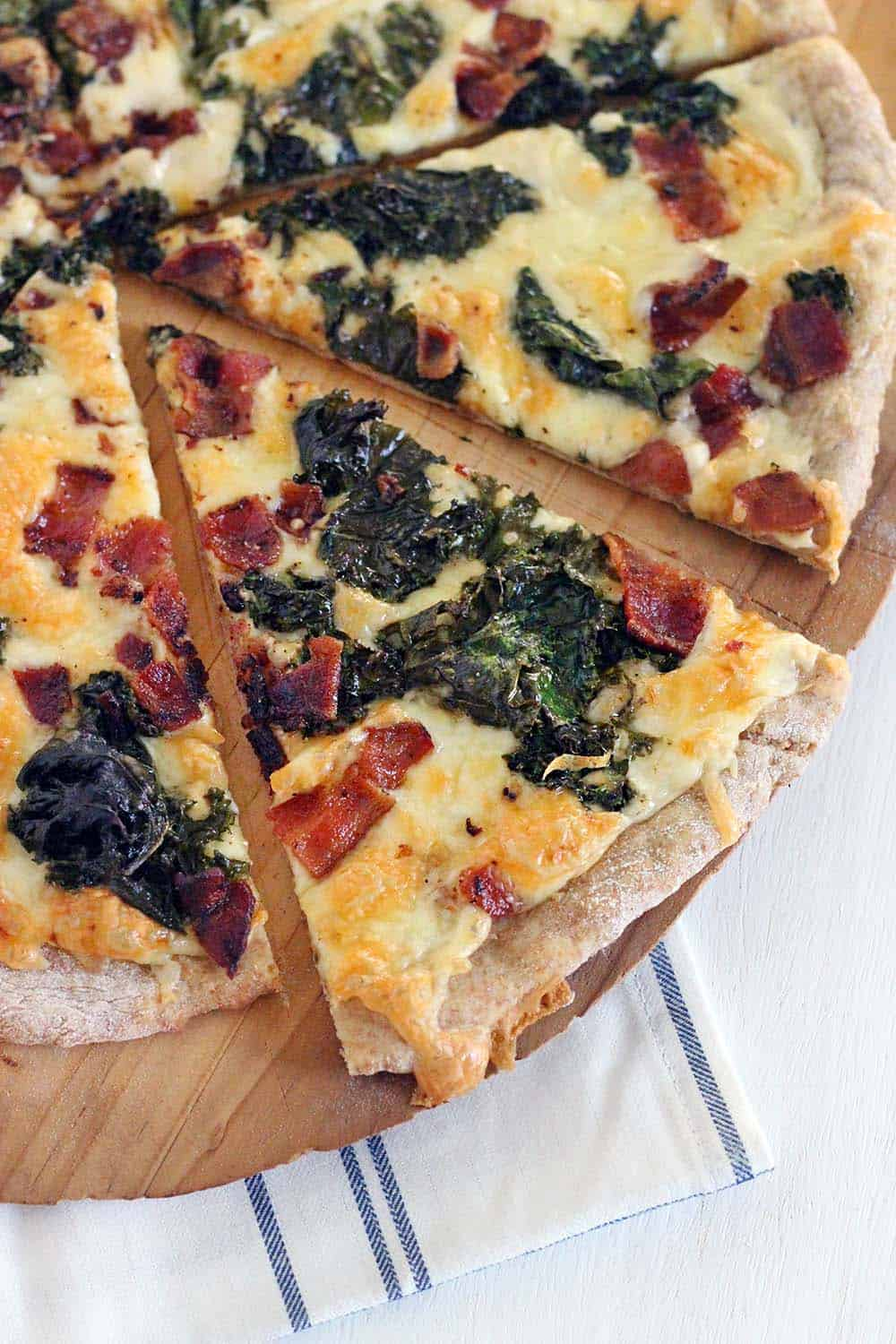 This Bacon and Kale Pizza is topped with super crispy kale and bacon pieces. This recipe comes together with only 5 ingredients in under 30 minutes!