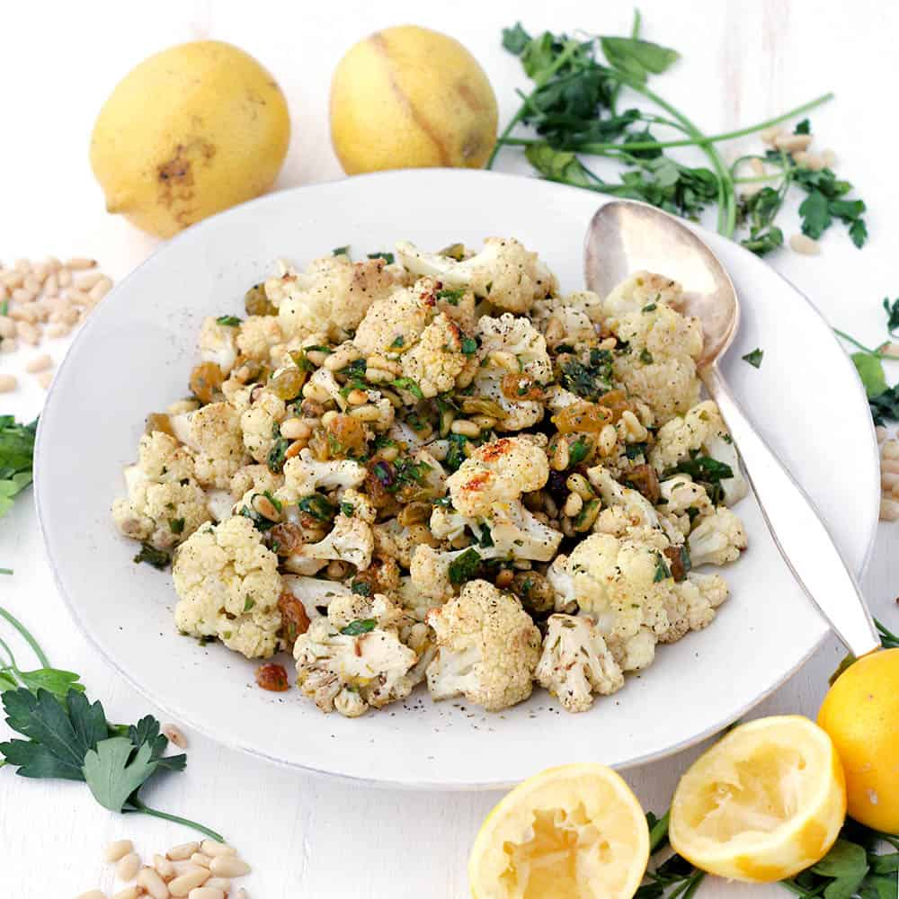This roasted cauliflower with pine nuts and raisins is a delicious side dish served warm or cold. Tossed with a lemon and olive oil vinaigrette and fresh parsley, it's a fresh Mediterranean recipe that goes with just about anything! Capers or olives can be substituted for raisins for a saltier, lower carb version.