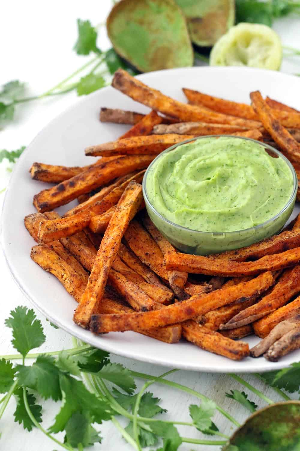 These crispy baked sweet potato fries are coated in chili powder, garlic, and a light coat of corn starch, which helps to make them crispy! Perfect for dipping into the cool, smooth, and creamy avocado cilantro sauce.