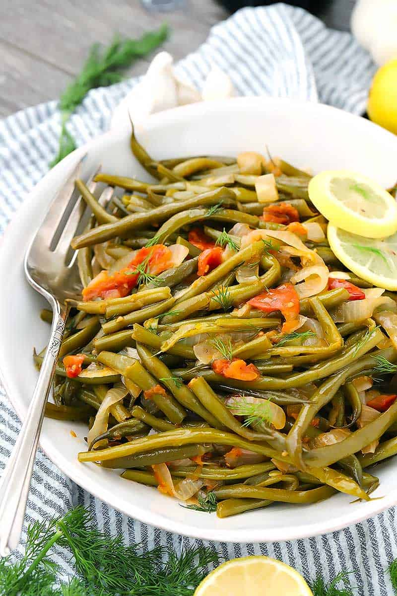 These Greek Green Beans(Fasolakia) are velvety tender, served in a tomato and garlic based sauce with lemon, dill, and plenty of extra-virgin olive oil. It's a great Mediterranean, low carb, paleo, and vegan side dish!