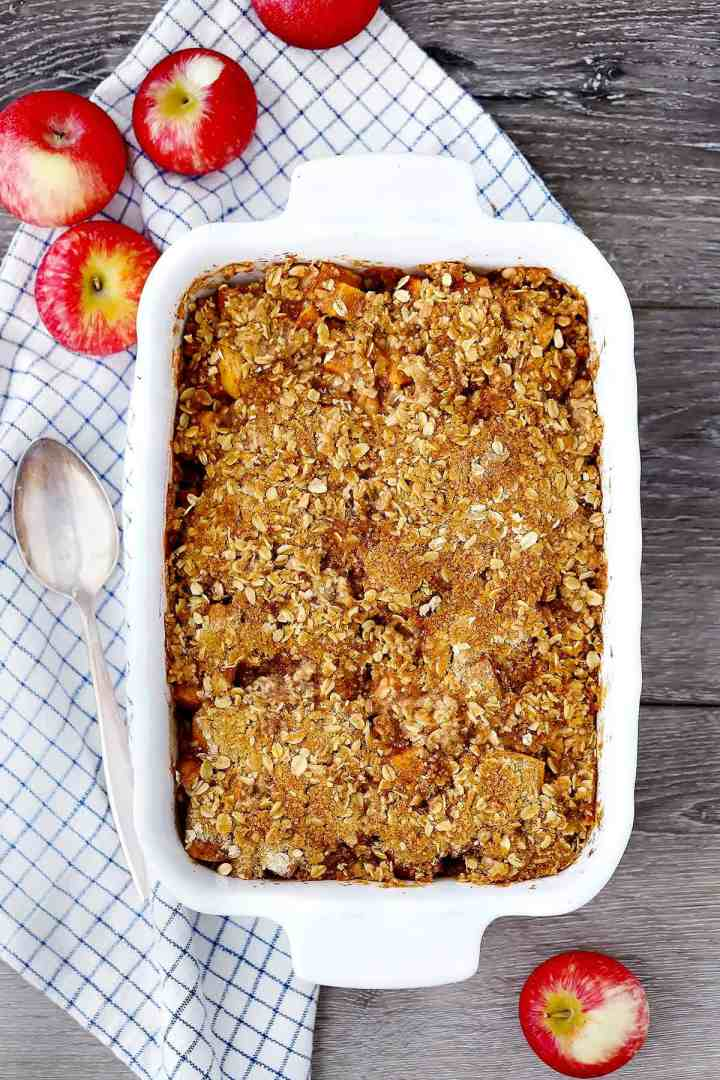 A baking dish with apple crisp on a plaid towel and apples around it.