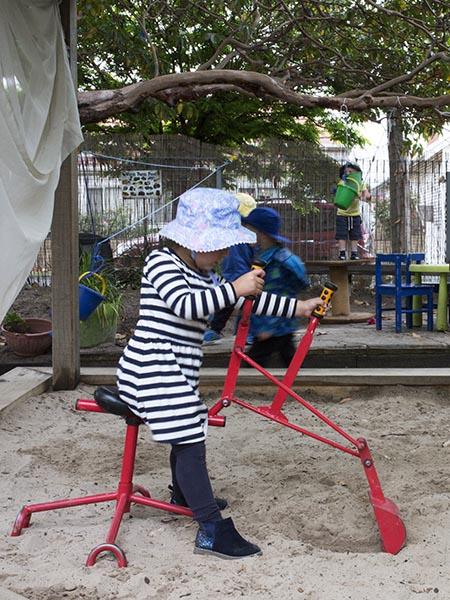 Child on Sandpit Digger in the North Room outdoor area at Batman Park Kindergarten