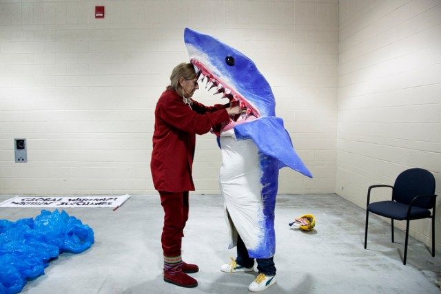 """Multi-discipline New York artist Pat Oleszko, left, helps Osmar Ramos-Caballero of Holyoke with his costume of a BP employee being eaten by a shark. Oleszko has a costume-themed """"Global Warning! Writhin' See/Change"""" group that will march in the annual First Night Grand Procession. ÒIÕm hard-hearted and a realist, but I have a functional sense of humor, so thatÕs how I deal with negativity,Ó Oleszko says. Participants for First Night prepared the day before New Year's Eve in Boston, MA on Sunday, December 30, 2012."""