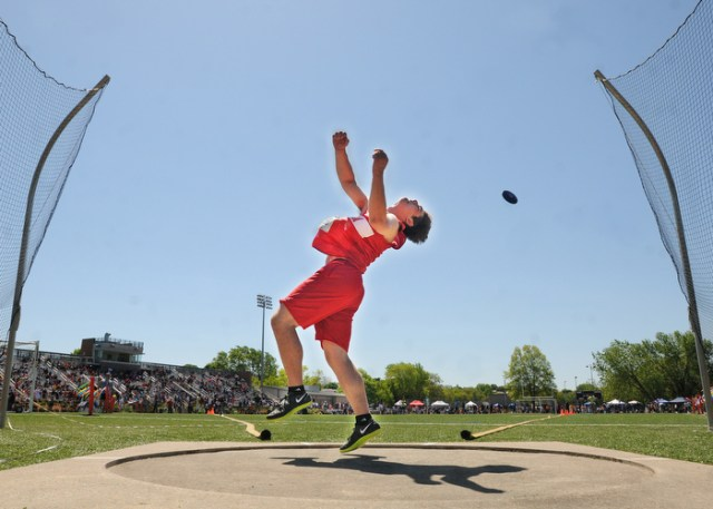 Somerville, MA - Hingham's Brian Sullivan 051212 releases a throw while working his way to victory during competition in the discus throw competition at MSTCA track & field invitational meet at Dilboy Stadium.