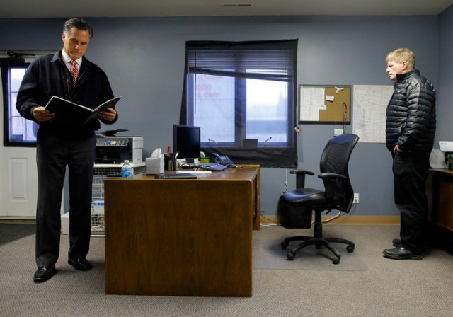 Republican presidential nominee Mitt Romney looks over his speech with senior advisor Stuart Stevens (R) in his hold room in Ames, Iowa before speaking at Kinzler Construction Services October 26, 2012.