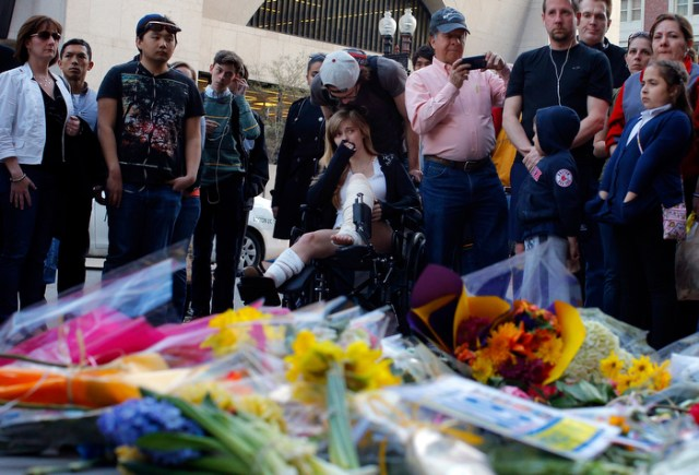 A Boston Marathon bombing survivor (C) visits the site of the first bomb explosion on Boylston Street in Boston, Massachusetts April 24, 2013.