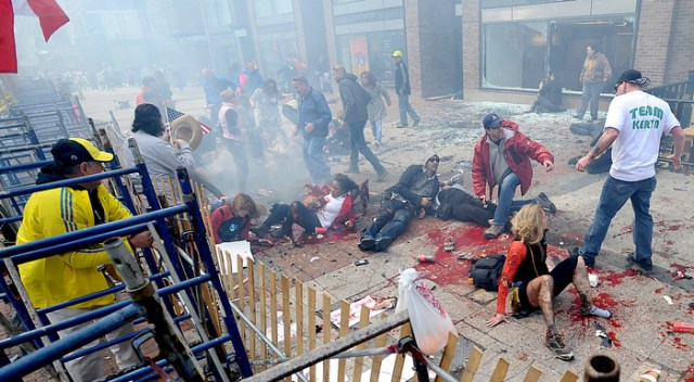 Smoke hovers over a chaotic scene of injured people and spectators along Boylston Street in Boston, just yards from the Boston Marathon finish line, after a bombing on April 15, 2013.