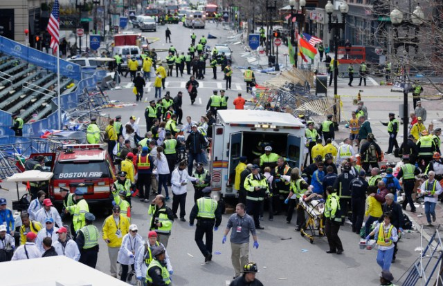 Medical workers aid injured people on Boylston Street at the finish line of the 2013 Boston Marathon following explosions in Boston, Monday, April 15, 2013.