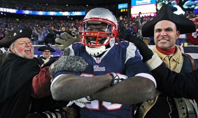 """Patriots running back LeGarrette Blount smiles and crosses his arms in satisfaction as he celebrates with members of the """"End Zone Militia"""" (a group of Minutemen who fire their muskets after every New England score) following his touchdown run in the fourth quarter. The New England Patriots hosted the Pittsburg Steelers in an NFL regular season game at Gillette Stadium."""