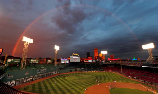Boston Red Sox players take batting practice as a rainbow appears in the sky above Fenway Park, before facing the St. Louis Cardinals in the World Series, Tuesday, Oct. 22, 2013.