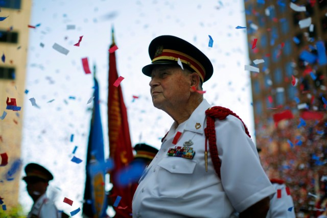 A member of the Ancient and Honorable Artillery Company stands amid confetti following a reading the United States Declaration of Independence, part  Fourth of July Independence Day celebrations, in Boston, Massachusetts July 4, 2013.