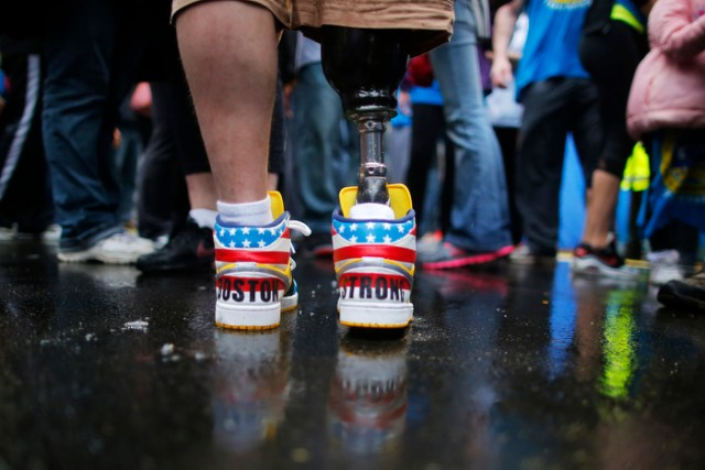 """The shoes of 2013 Boston Marathon bombing survivor J.P. Norden read """"Boston Strong"""" as he stands at the finish line on the one-year anniversary of the bombings in Boston, Massachusetts April 15, 2014.  J.P. and his brother Paul, also a bombing survivor, took part in the final portion of the """"Legs for Life Relay"""", joining family members and friends who walked the entire Marathon route to raise money for children needing prosthetic limbs."""