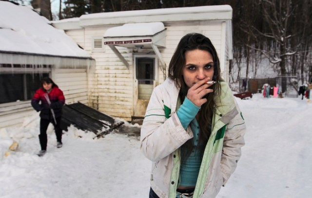 "Pownal, VT -  Friday, Feb. 7, 2014:   Brianna Wasieleuski, 11, left, looks on as her sister, recovering heroin addict  Stephanie Predel, 23, right, has a smoke outside their rental house.   Federal studies show that Vermont has one of the highest per capita uses of illicit drugs. ""There's just nothing here,"" said Stephanie Predel, 23, who went from painkillers to heroin, hiding her habit from her children by shooting up in the bathroom. ""Come wintertime, everybody just sits inside using."" Stephanie, who says she has not used heroin since November, has lost custody of her children. She has no job and no home and for now is staying with her mother, Jennifer Rose, 42, who blames herself for her daughter's descent into drugs. ""Because I had a dysfunctional family growing up, I did a poor job of bringing her up,"" Ms. Rose said. She said she did not know how to break the cycle."