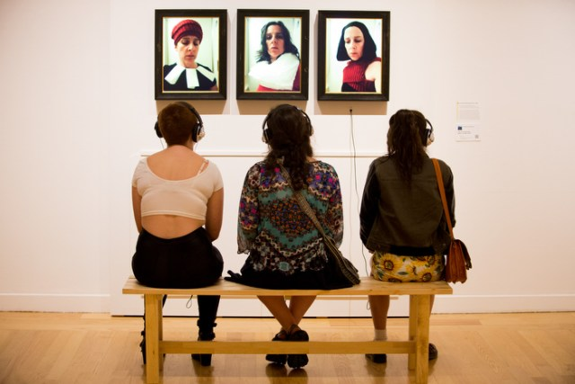 At the Koppelman Family Gallery, three guests admire a series of video portraits in the Aidekman Art Center on September 11th, 2014.