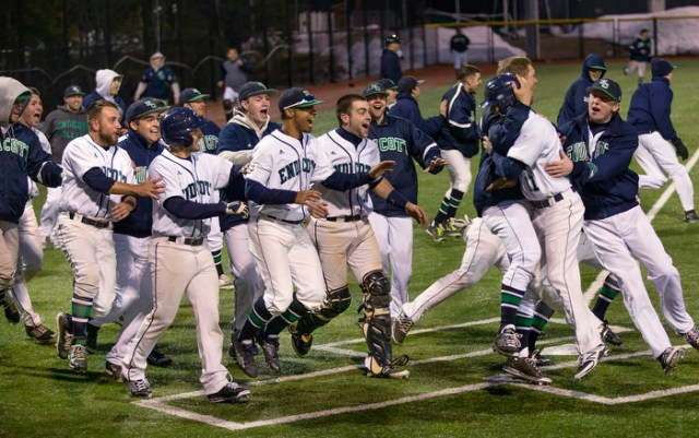 Nick Berno is hugged by Michael Cahill, as his teammates join the celebration, after scoring the winning run in the bottom of the 11th inning of a scoreless tie at North Field, Beverly, MA. Endicott defeated Eastern Nazarine College 1-0, sweeping a doubleheader.