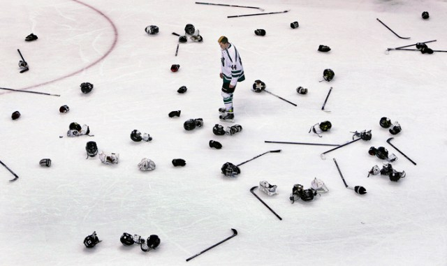 03/15/15: Boston MA: After the Westwood players celebrated their victory over Concord-Carlilse for the Division Two Boy's title, Westwood senior forward Patrick Forde faced a tall task as he looks for his discarded equipment amoung the multitudes of items littering the ice surface.