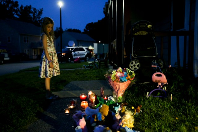A young girl stands next to the make-shift memorial in front of am Auburn home where a 2-year-old foster child died on Aug 17, 2015.